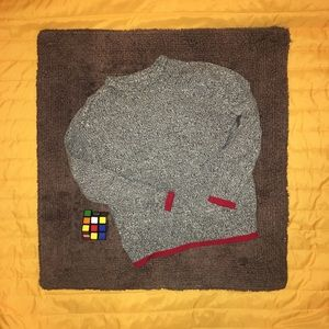 Heathered grey sweater with red trim.